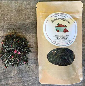 "There is a small circular mound of loose leaf tea on the left side of the photo and a brown bag labeled ""raspberry green loose leaf tea"" to the right. Pictured against a wooden backdrop."