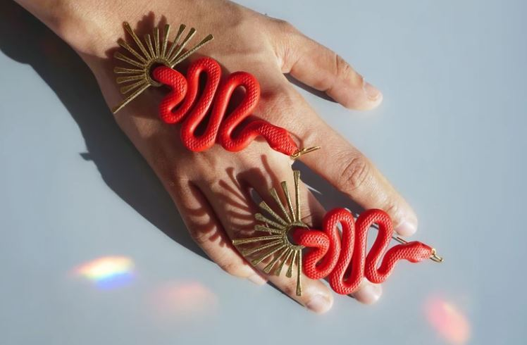 Pictured against a blue background and model's hand are a pair of red, clay earrings. The earrings are shaped into the form of a snake with golden fan shaped detail at the bottom.