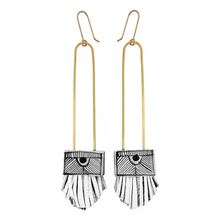 Load image into Gallery viewer, Pictured against a white background are a pair of long, gold wired earrings. The bottoms of the earrings have a square white ceramic base with handpainted black stripes on them. There are white leather tassels at the bottom.