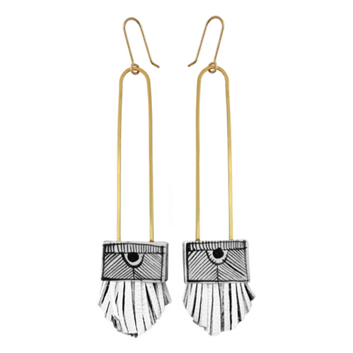 Pictured against a white background are a pair of long, gold wired earrings. The bottoms of the earrings have a square white ceramic base with handpainted black stripes on them. There are white leather tassels at the bottom.