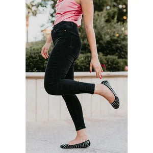 model in black pants and a pink shirt with black studded ballet flat