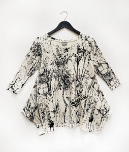 flowy ivory top with a black branch print pullover top with 3/4 sleeves and a draped hemline.