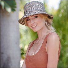 Load image into Gallery viewer, Model wearing a black, white, and natural bucket straw hat with a tank top and gold jewelry in a tropical setting.
