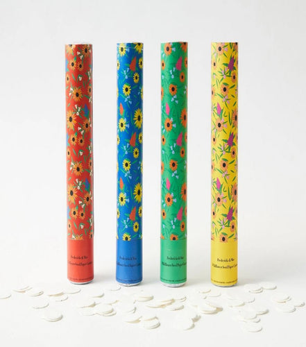 Pictured against a white background are four standing cylinder shaped seed cannons. They are colored from left to right as followed: red, blue, green, and yellow. The labels all have floral print on each respective cylinder.