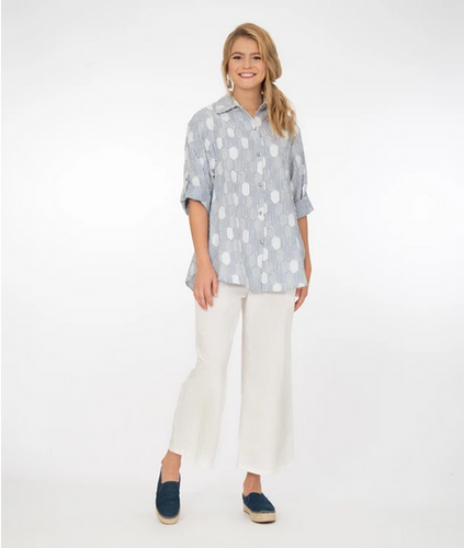 blonde model with side pony tail wearing blue an white stripe button-up blouse, white wide leg pants, and dark navy espadrilles. against a white background