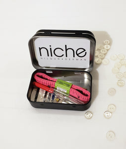 miniature sewing kit in a black tin box that inlcudes, thread, buttons, safety pin, measureing tape, seam ripper and sewing needle