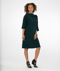 model in a dark green dress with an asymmetrical sleeve and neckline