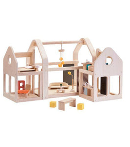 Wooden dollhouse with open plan featuring furniture and multiple pieces. Pictured against a white backdrop.