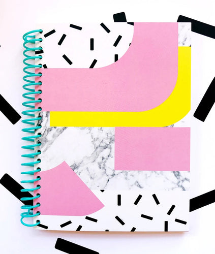Pictured against a white background with thick black accent lines is a notebook. The notebook features a turquoise colored coil binding. The cover of the notebook features thick pink and yellow curves on it, a black and white marbled center, and the top and bottom are white with small black flecks spread throughout.