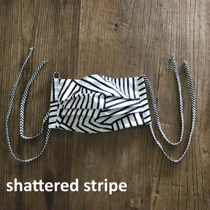 Pictured against a wooden background is a face mask that features a black and white striped print and four fabric ties.