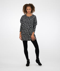 model in a grey tunic with black square print and pockets at the hip