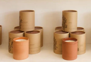 Two separate stacks of candles packaged in circular cardboard packaging with candles encased in terra cotta in front of stacks.