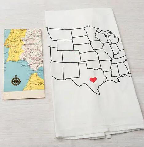 Photo of a white linen tea towel with the United States of America printed on it laying next to a paper map. There is a red heart in the center of Texas