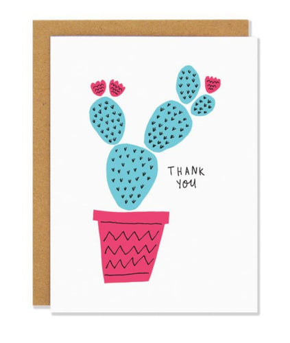Pictured against a white background is a brown envelope with a white card on it. There is a hand drawn illustration of a green prickly cactus inside of a pink pot. There are also three pink cactus flowers on the cactus and text that says
