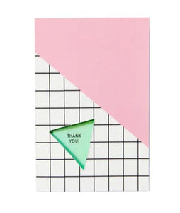 "Pictured against a white background is a card that features a black and white grid pattern at the bottom and a light pink filler at the top. There is a mint colored triangle with the words ""thank you!"" written on it."