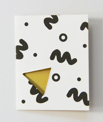 Pictured against a white background is a white card that features thick squiggly lines and circles on it. There is a yellow triangle cutout on the front of the card.