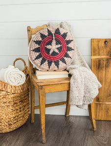 Round basket inspired printed pillow with accents of red and navy blue sitting atop a wooden chair.