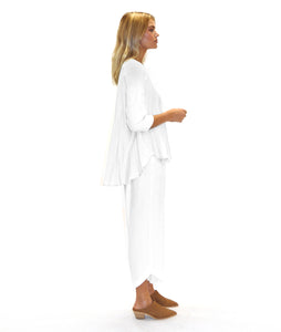 model in a white pull over top with a flowy high-lo hem, with white pants and tan shoes