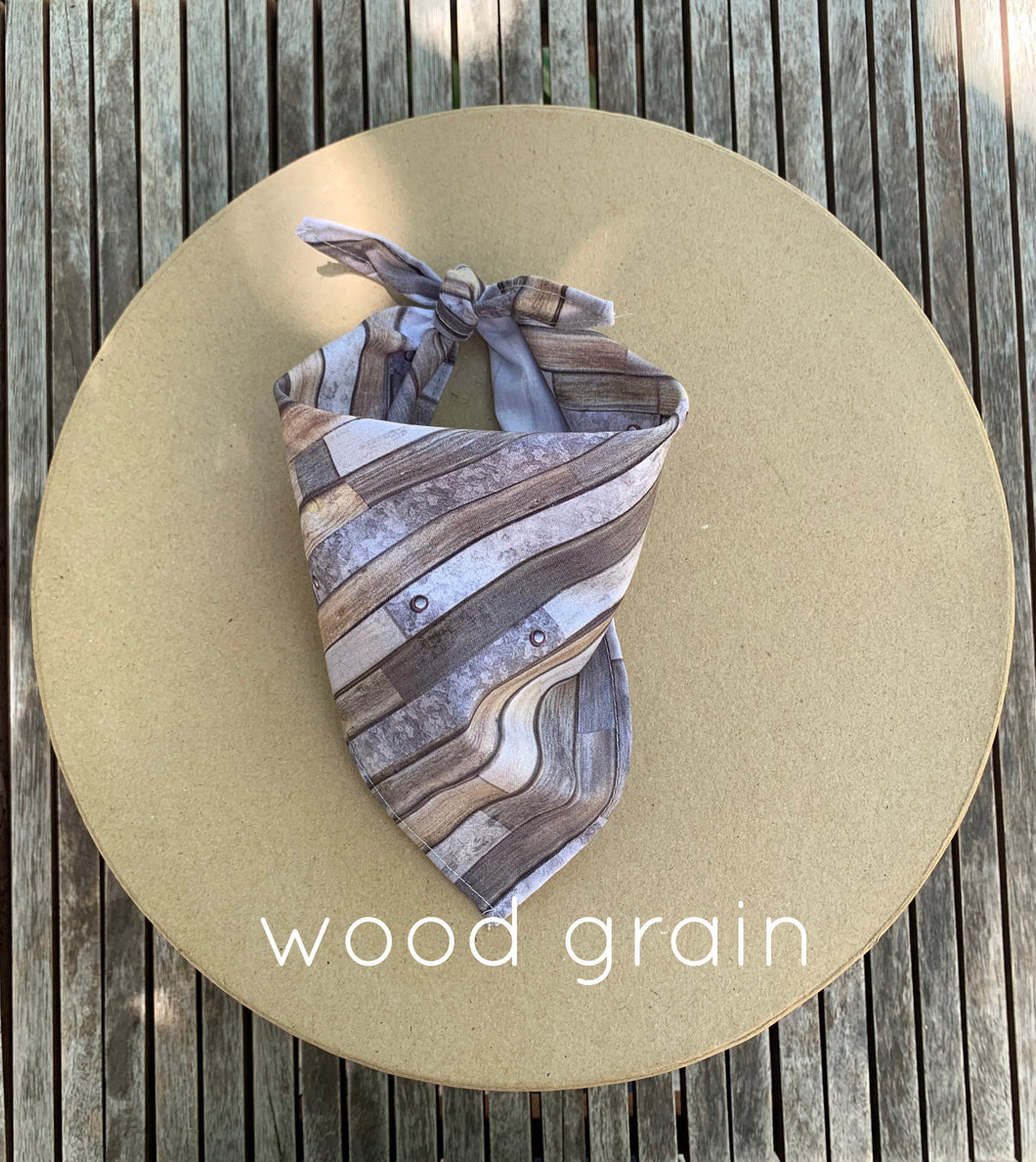 Pictured on a coardboard circle, is a small dog bandana with wood grain print.