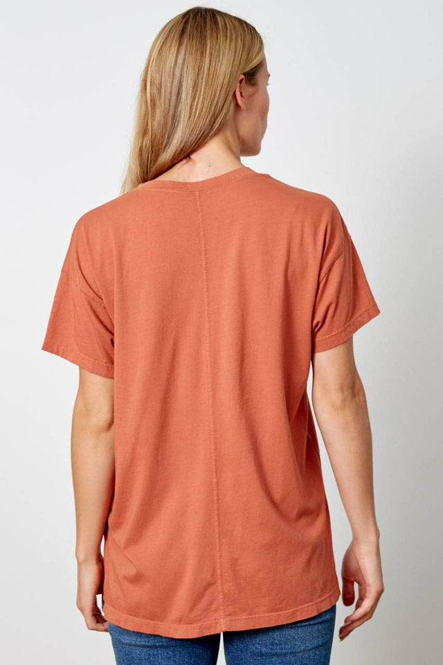 Women's crewneck t-shirt in burnt orange. Has a relaxed fit, split side seams, and center seam down back.