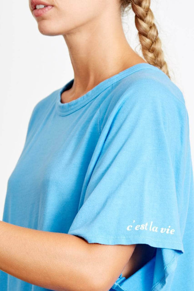 "bright blue, raglan short sleeve t-shirt. Loose fit with ""c'est la vie"" printed in white on the left sleeve"