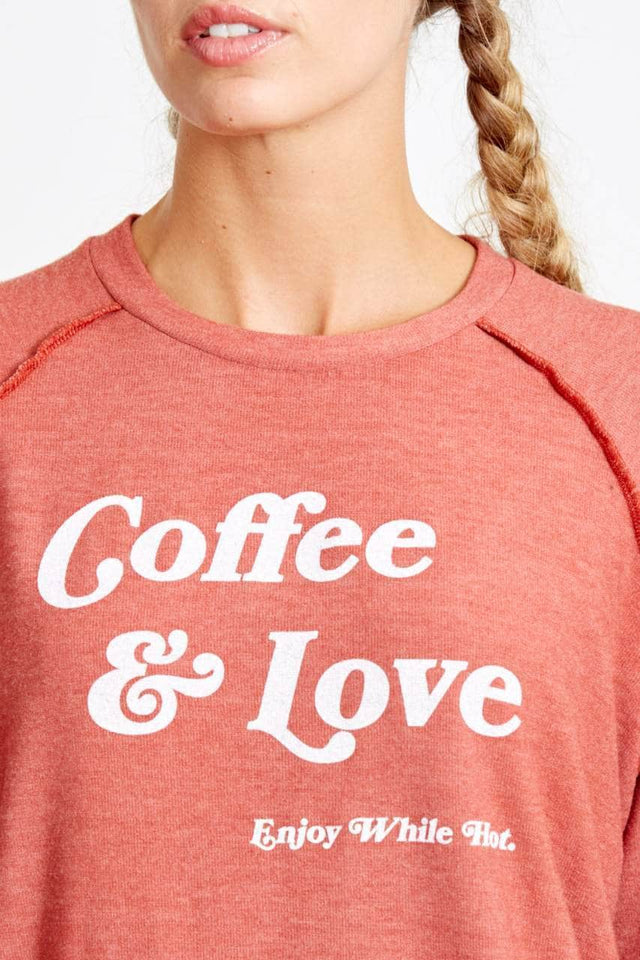 red-orange sweatshirt made of brushed hacci with exposed seam detail and white coffee & love enjoy while hot graphic on front