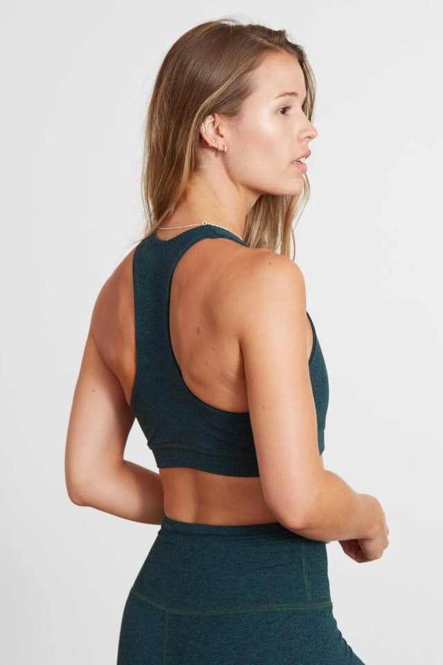 "emerald green racerback sports bra with ""SWEAT MORE. GET MORE."" printed in white across the chest"