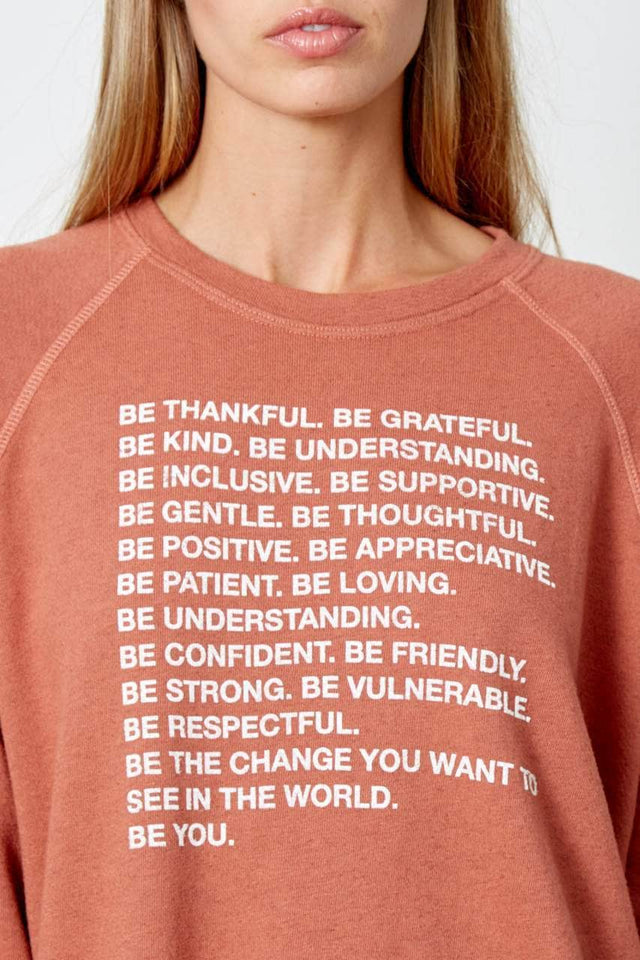 "burnt orange sweatshirt with raglan sleeves. Fits loose and hits just past the hip. Graphic printed in white on front reads ""Be Thankful. Be Grateful. Be Kind. Be Understanding. Be Inclusive. Be Supportive. Be Gentle. Be Thoughtful. Be Positive. Be Appreciative. Be Patient. Be Loving. Be Understanding. Be Confident. Be Friendly. Be Strong. Be Vulnerable. Be Respectful. Be the change you want to see in the world. be YOU."