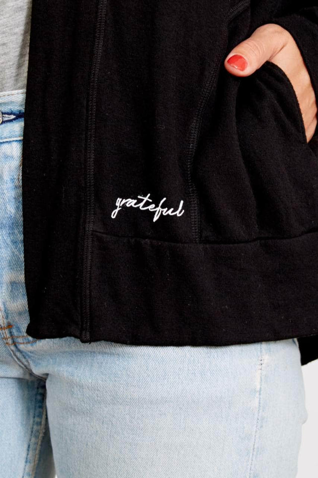 black shawl collar cardigan with pockets and grateful printed in cursive on front left pocket