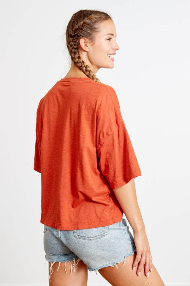 "boxy fit orange toned t-shirt with dropped shoulder sleeves that hit at the elbow. Square outlined graphic featuring a sunshine and wave. ""Live your way everyday"" is printed in all caps in white, along the top edge of the wave."