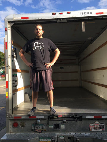 "Photo of a man in a black ""Mimi's Attic"" t-shirt standing in the back of an empty moving truck."