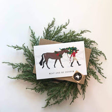 "Load image into Gallery viewer, CARD AND ENVELOPE SET WITH HORSE AND RIDER CARRYING CHRISTMAS TREE. TEXT READS ""EAT AND BE MERRY"""