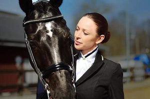 Black horse with rider wearing the white satin stock tie with the black crystals