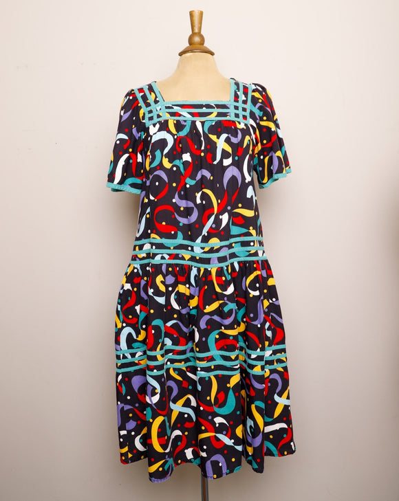 1990's Black Muumuu Midi dress with primary colored celebration confetti print and bell sleeves with pockets