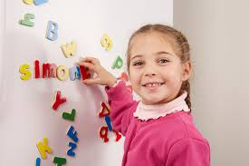 Little girl with a big smile and playing with abc magnet letters on a white fridge front