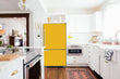 Load image into Gallery viewer, Full Kitchen Layout Wood Floors Shoolbus Yellow Magnet Skin on Refrigerator Model Type Bottom Freezer Next to Recessed Microwave Surrounding White Cabinets and White Countertop