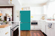 Load image into Gallery viewer, Full Kitchen Layout Wood Floors Teal Turquoise Magnet Skin on Refrigerator Model Type Bottom Freezer Next to Recessed Microwave Surrounding White Cabinets and White Countertop