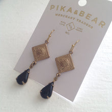 Load image into Gallery viewer, Spanish, and Moroccan influenced drop earrings feature raw brass diamond shaped stampings, and vintage black glass teardrop settings.