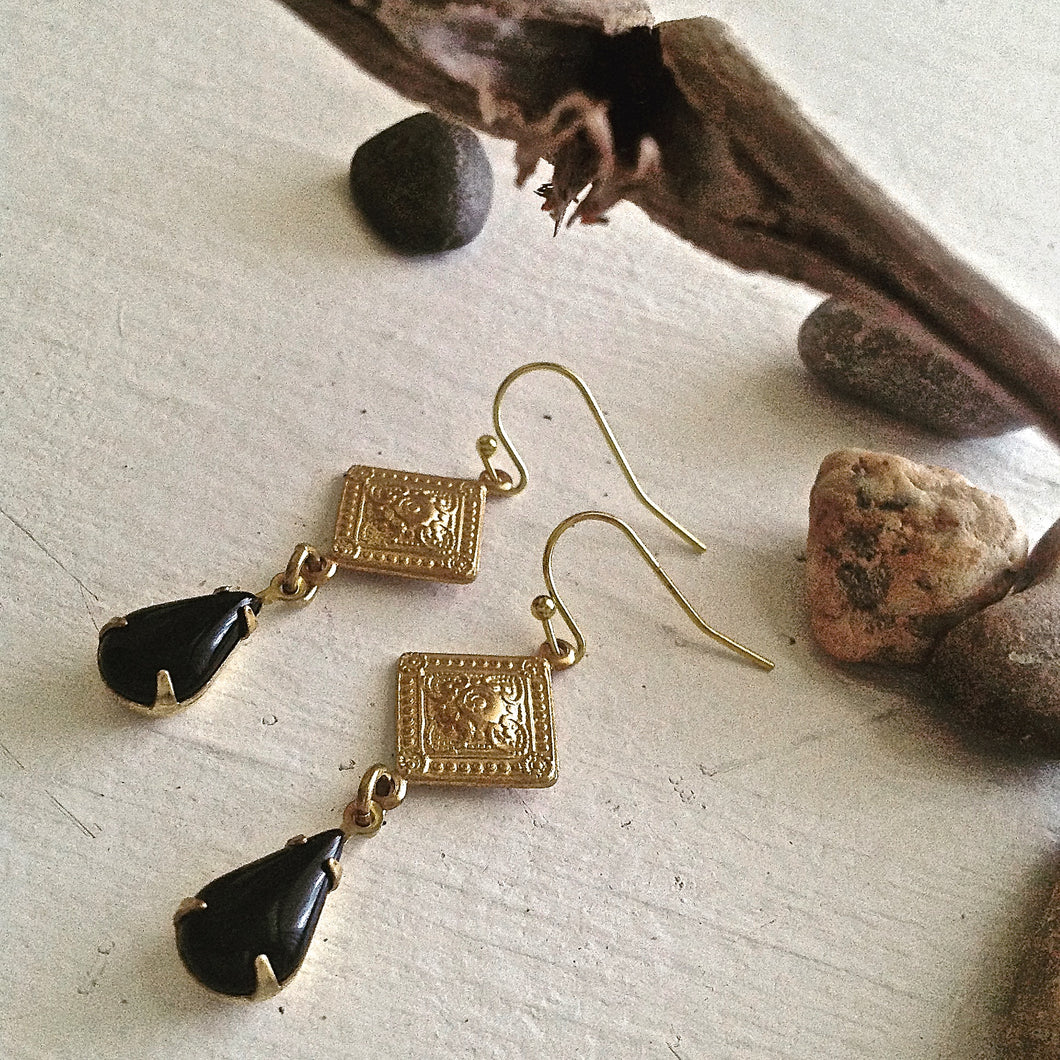 Spanish, and Moroccan influenced drop earrings feature raw brass diamond shaped stampings, and vintage black glass teardrop settings.