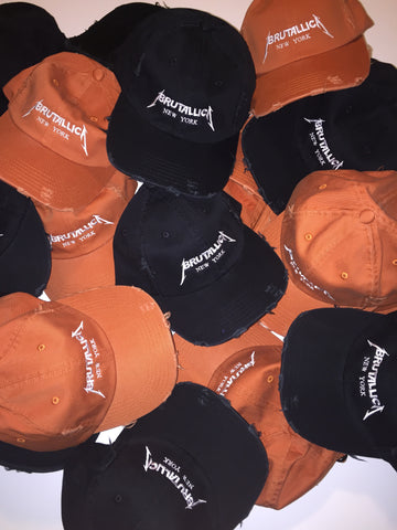 Brutallica distressed dad hats in black and burnt orange colorways with white embroidered logo pile of hats
