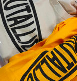 Brutallic Streetwear bubble tea tshirts with oval front logo, and buddha on the back, khaki tan beige color and mustard yellow color shirt close up of front tossed shirts