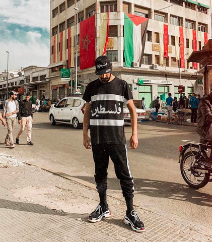 Palestine cut and sew shirt worn by male model in morocco in the streets with flags in the background, wearing brutallic shirt and hat with balenciaga shoes