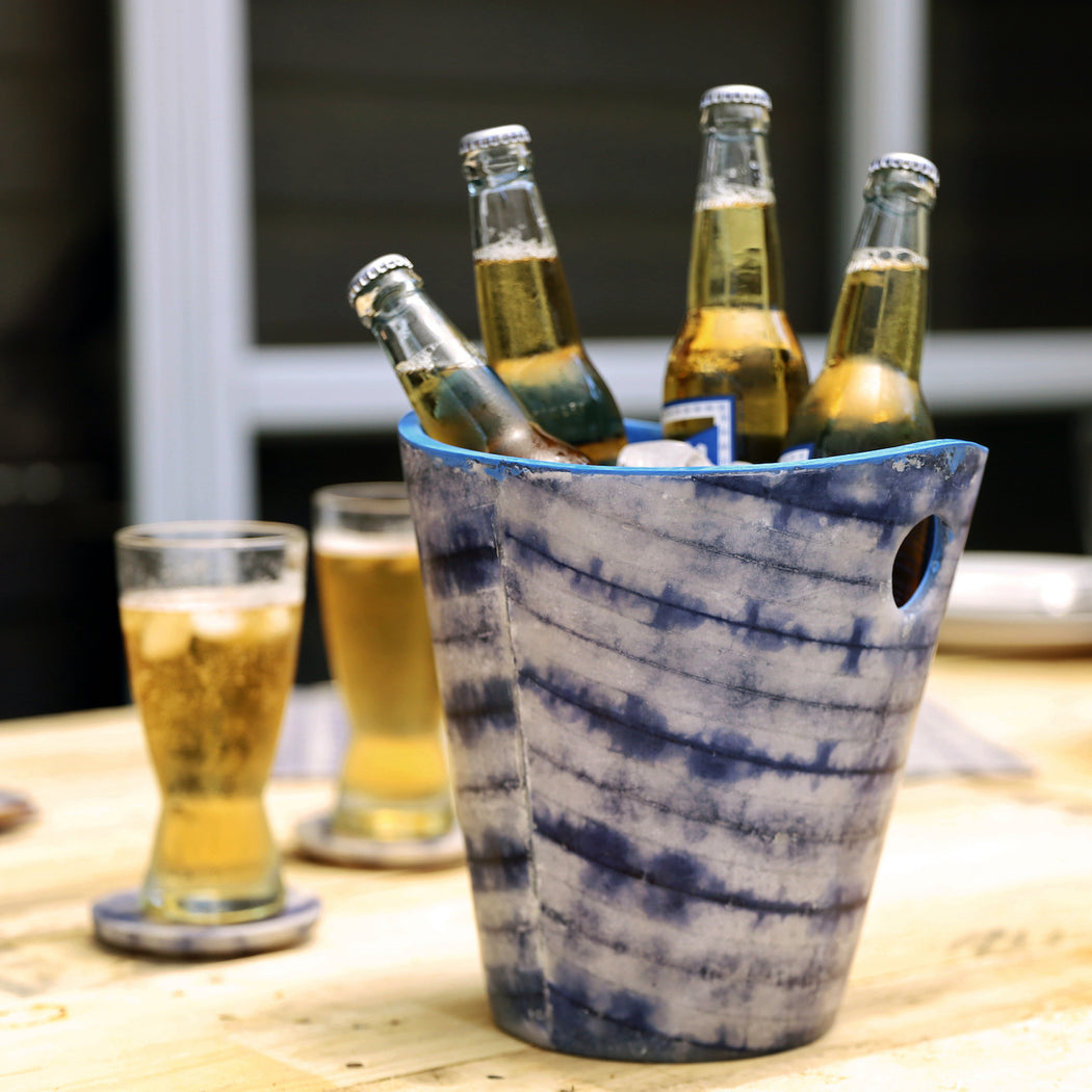 Our Shibori tie-dye beer and ice bucket lends summer chic to icing down beverages at your intimate backyard activities. Shibori tie-dyed paper is meticulously laminated with resin material in the Philippines. Available online.