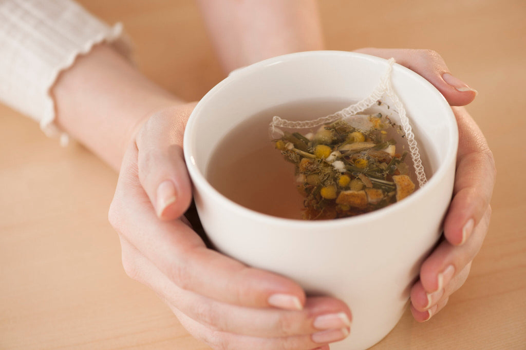 Chamomile tea with person holding in between two hands