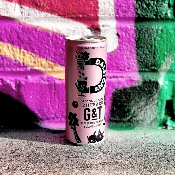 Graffiti wall background with a pink can of Dalston's rhubarb G&T in front of it.