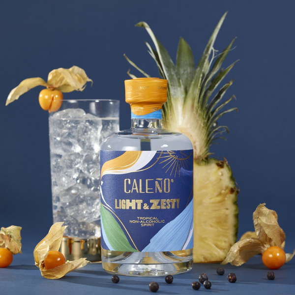 Navy blue background featuring a glass of Caleno alcohol free spirit and a pineapple cut in half. In the front is a bottle of Caleno's Lighty and Zesty alcohol free spirit.