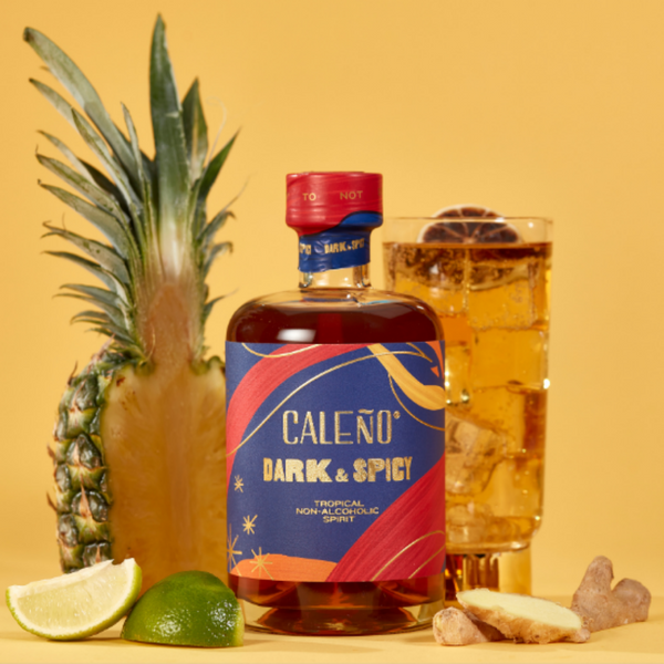 An orange background features a pineapple cut in half and a cocktail. In the foreground is a bottle of Caleno's Dark and Spicy non-alcoholic spirit along with cut up limes and a piece of ginger.