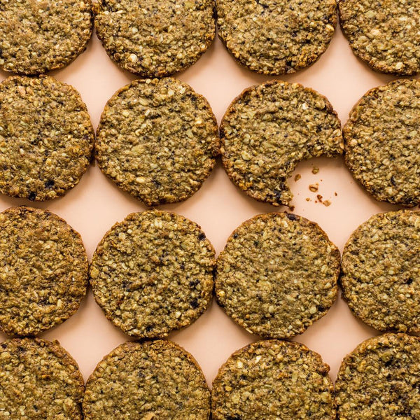 12 Wholey Moly cookies pictured out of their packets lined up in three rows of four. The third cookie on the first row has had a bite taken out of it. They are laid on a peach background.