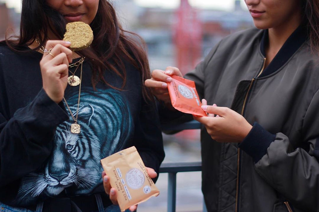 Two women wearing black clothing are holding Wholey Moly cookies. Woman on the left of the photo has taken a bite out of her cookie and is holding its brown packaging. Woman on the right has not yet taken her cookie out of its orange packaging and holds it in her hands.