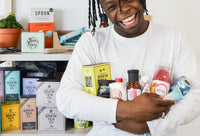 Mighty Small | Discover New Food & Drink | Gifts & Home Delivery - Person holding food and drink products and smiling